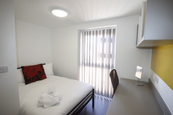 Bedroom inclusive of a desk in this serviced apartment